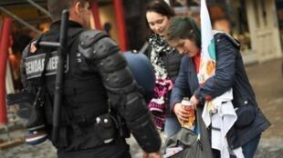 Un policier inspecte le sac d'une étudiante manifestante à Nantes, le 27 mars 2018.