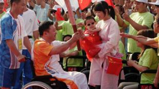 Liu Zhengwei (dans son fauteuil roulant), l'un des derniers relais de la torche paralympique avant l'ouverture des Jeux de Pékin, le 6 septembre.