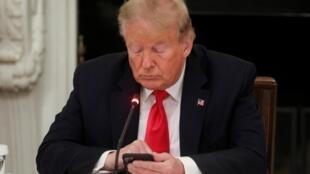 Donald Trump consultant son «smartphone» (ses tweets?) lors d'une réunion à la Maison Blanche, le 18 juin 2020.