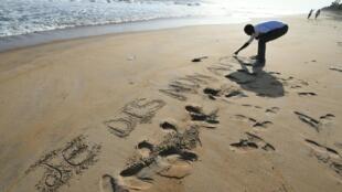 Sur la plage de Grand-Bassam, un homme écrit dans le sable «Je dis non au terrorisme», le 16 mars 2016.