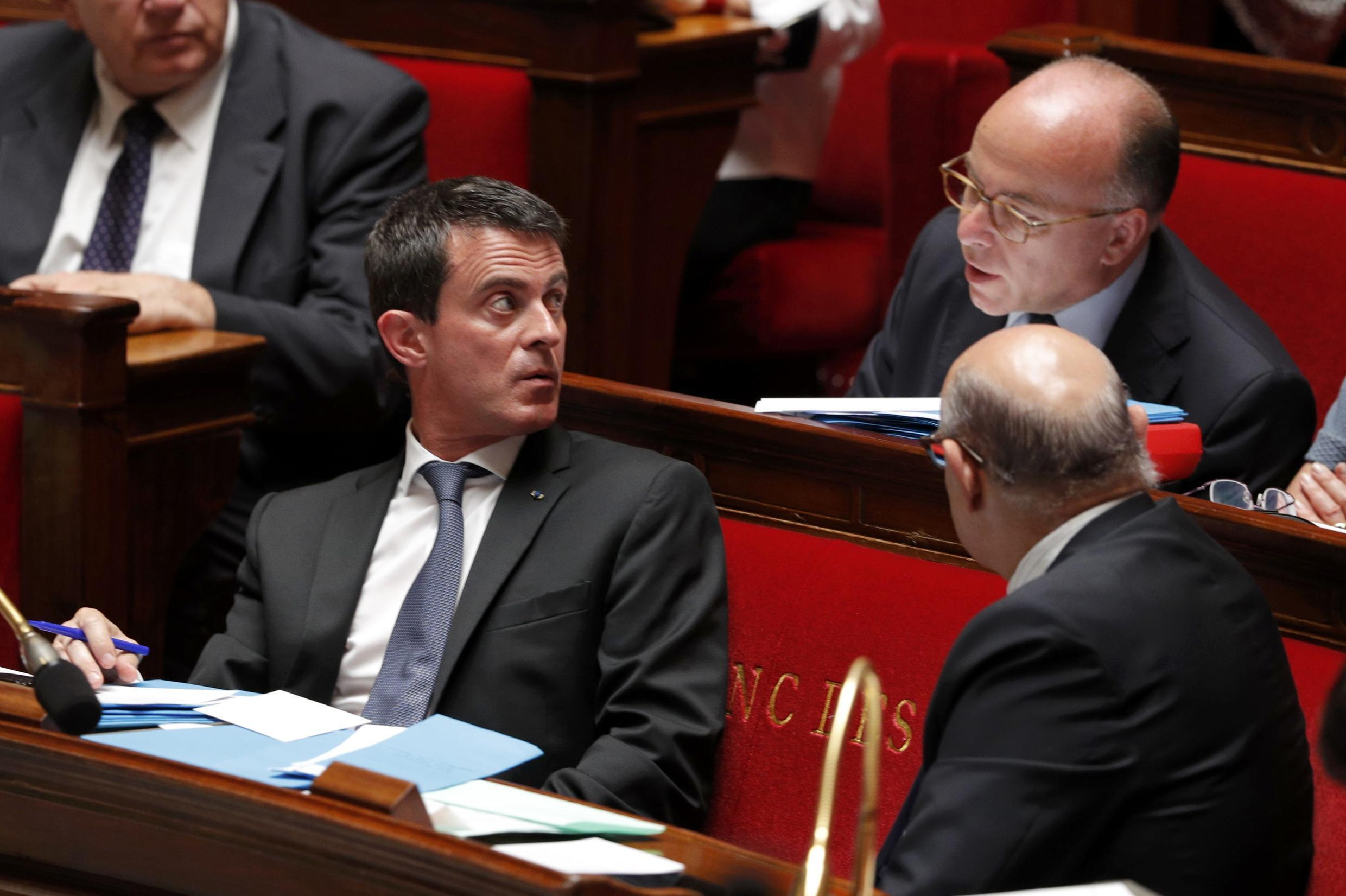 French Prime Minister Manuel Valls (L) speaks with Interior Minister Bernard Cazeneuve during the parliamentary debate on the state of emergency