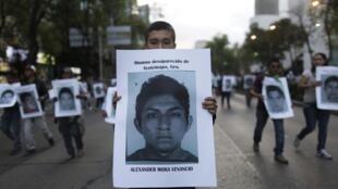 Um manifestante leva um cartaz com a foto de Alexander Mora Venancio, um dos 43 estudantes desaparecidos.