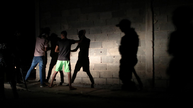 Des membres de la Force d'action spéciale de la police nationale vénézuélienne (FAES) arrêtent des personnes lors d'une patrouille de nuit, à Barquisimeto, au Venezuela, le 20 septembre 2019.