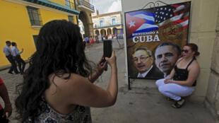 Une touriste californienne pose devant l'affiche des présidents  americain Barack Obama et  cubain Raul Castro, le 19 mars 2016.