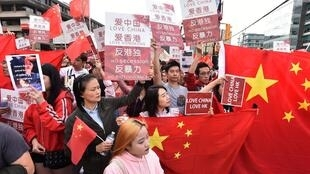 De nombreux Chinois ont participé à des contre-manifestations face aux manifestations hongkongaises le 17 août 2019 notamment au Canada comme ici à Vancouver. Ils sont aussi nombreux à prendre un selfie devant le drapeau chinois.