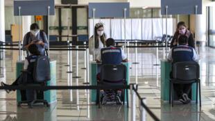 Passageiros passam pelo controle sanitário anticovid ao desembarcarem no aeroporto internacional Arturo Merino Benítez, em Santiago. 21/12/2020
