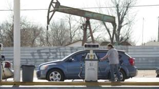 Esta imagen de archivo, tomada el 12 de febrero de 2016 en Oklahoma City, Oklahoma, muestra una estación de servicio próxima a un pozo petrolero