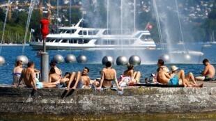 As pessoas aproveitam o clima ensolarado do verão nas margens do Lago Zurique, em Zurique, Suíça