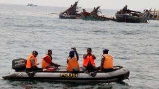 Des policiers indonésiens passent près de restes de bateaux explosés qui ont été pris en train de pêcher illégalement.