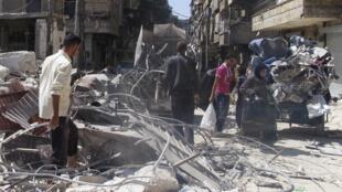 Des civils syriens dans les ruines d'un bâtiment détruit par un bombardement à Alep, le 9 septembre dernier.