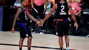 Kawhi Leonard (derecha) saluda a su compañero de los Clippers Lou Williams en su camino al banquillo en el último cuarto del séptimo partido de las semifinales del Oeste ante los Denver Nuggets.