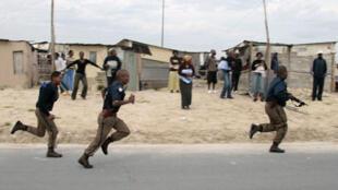 Le bidonville de Khayelitsha, le 23 mai 2008. La police poursuit des pillards lors d'un débordement de violence anti-étrangers.