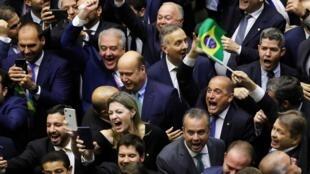 Membros do Congresso e apoiadores do projeto de reforma da aposentadoria, celebram a votação durante sessão para votar o projeto de reforma da aposentadoria na Câmara dos Deputados em Brasília, Brasil, 10 de julho de 2019.