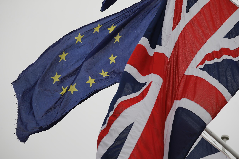 Esta imagen de archivo muestra una bandera europea ondeada por un manifestante anti Brexit junto a una bandera del Reino Unido izada en un asta frente al Parlamento británico en Londres, el 30 de enero de 2020