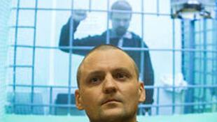Сергей Удальцов в зале суда, Леонид Развозжаев виден на экране телетрансляции