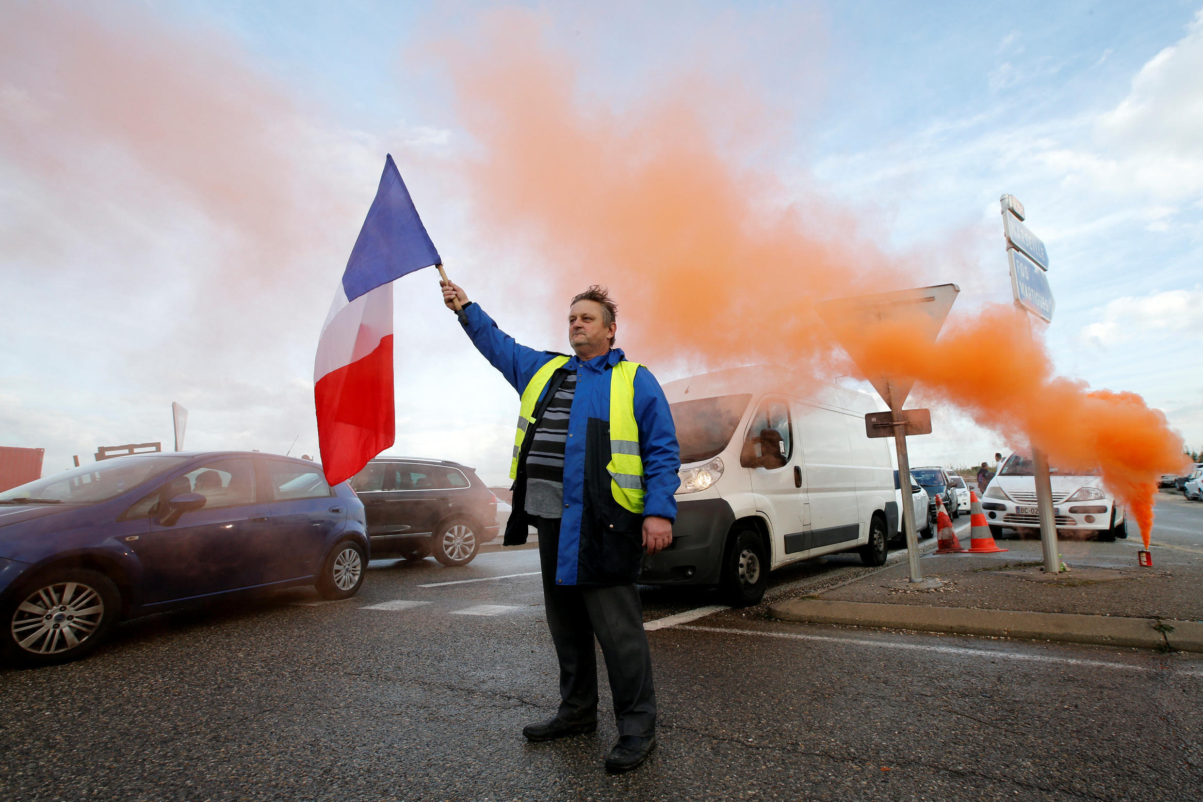A demonstrator wearing yellow vests, a symbol of a French drivers' protest against higher fuel prices, holds a French flag as he blocks the access to the Total biodiesel refinery at La Mede near Fos-sur-Mer, France, November 22, 2018.