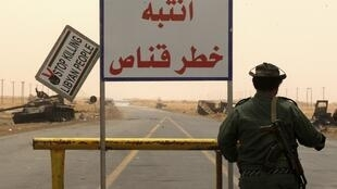 """A rebel fighter stands guard by a sign that reads in Arabic """"beware of snipers"""" the road between Ajdabiyah and Brega"""