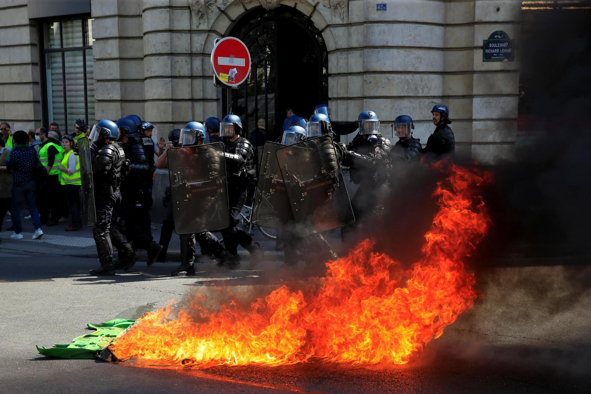 Police officers pass a fire at a demonstration during Act XXIII (the 23rd consecutive national protest on Saturday) of the yellow vests movement in Paris, France, April 20, 2019.