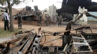 Soldats français nettoyant les débris d'un véhicule militaire détruit lors du bombardement du 6 novembre 2004, à Bouaké, en Côte d'Ivoire.