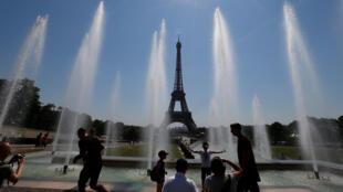 Parisiens et visiteurs se rafraichissent dans les bassins publics en face de la tour Eiffel, le 3 août 2018.