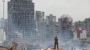 A Lebanese soldier stands near the site of the double explosion which devastated Beirut.