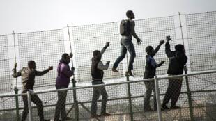 Des migrants africains escaladent le grillage surmonté de lames de rasoir, frontière entre l'Espagne et le Maroc, dans l'enclave espagnole de Melilla.
