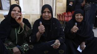 Trois femmes égyptiennes qui ont voté le 5 décembre montrent leurs doigts tachés de l'encre qui a permis de prendre leurs empreintes digitales.