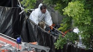 Investigators carry a stretcher with a body bag from the house where a human body part was found in Nantes 21 April 2011