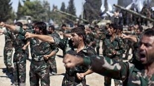 Des combattants rebelles paradent lors d'une cérémonie d'unification dans une ancienne académie militaire du nord d'Alep, le 13 septembre 2013.