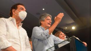 El presidente electo de Ecuador, Guillermo Lasso (centro), habla a la prensa junto a su esposa María de Lourdes Alcívar (derecha) y el exalcalde de Guayaquil Jaime Nebot, tras conocer los resultados preliminares de las elecciones en Ecuador, el 11 de abril de 2021, en Guayaquil