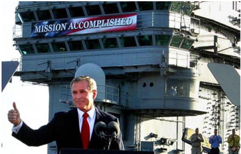 """2003年5月,伊拉克戰爭爆發後,時任美國總統小布什登上""""林肯""""號航母發表講話。在他的身後,航母指揮塔上掛着巨幅""""任務完成""""的標語。"""