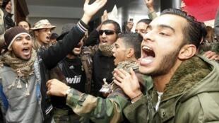 D'anciens rebelles libyens réclament leur solde impayée au Premier ministre, le 23 décembre 2011 à Tripoli.