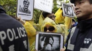 Ativistas mostram fotos de dissidentes chineses capturados pelo regime, em frente à embaixada americana, em Taipei.