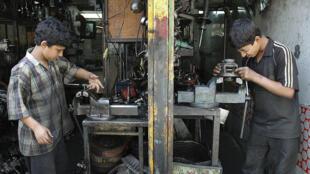 Deux enfants, dans un atelier de mécanique, à Téhéran