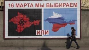 Une femme passe devant une affiche de la campagne pour le référendum d'autodétermination du 16 mars en Crimée, à Sébastopol, le 10 mars 2014.