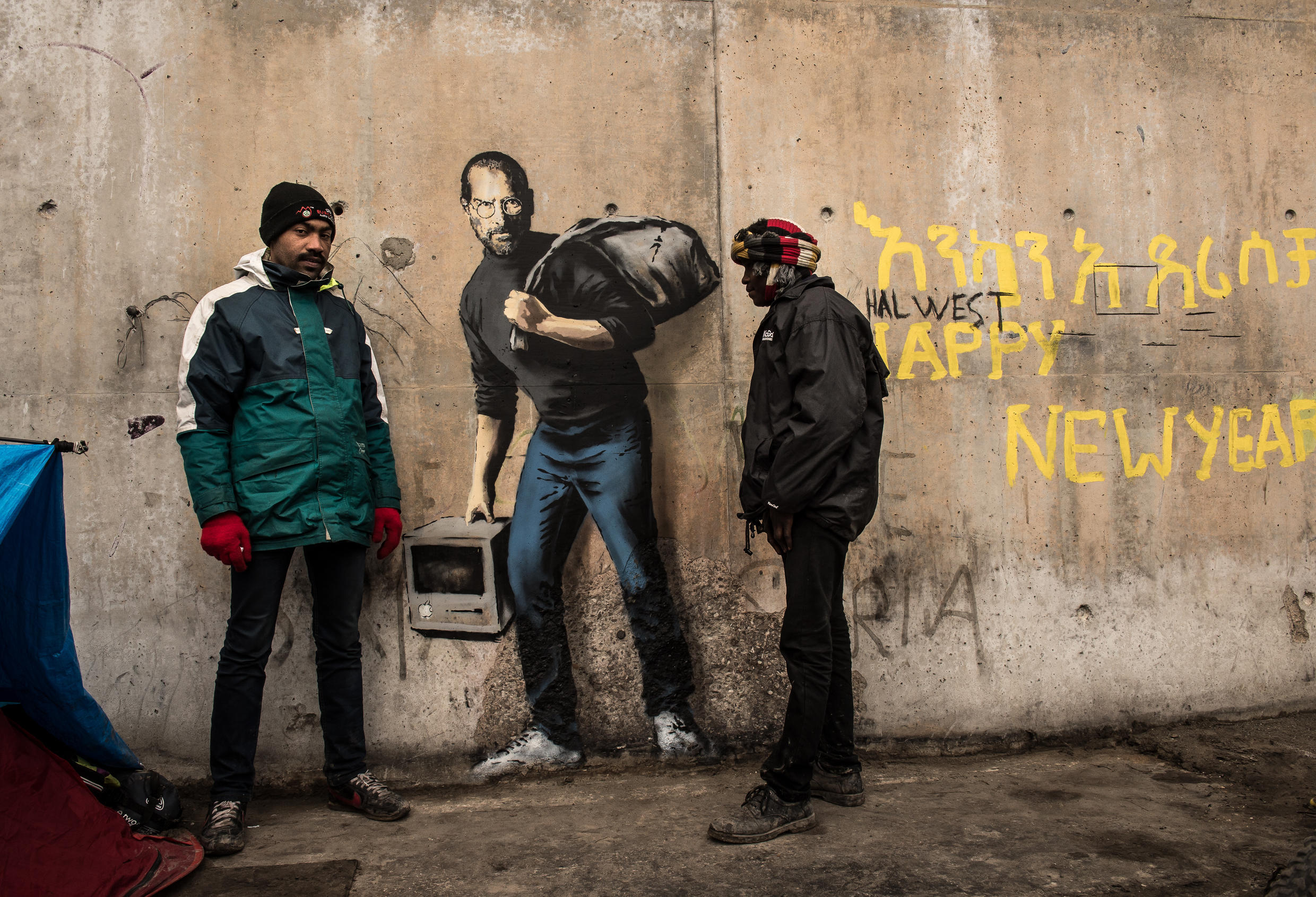 """Two men stand next to a street art graffiti by elusive British artist Banksy representing Steve Jobs, founder and late CEO of Apple, at the migrant camp known as the """"Jungle"""" in Calais, northern France, on December 12, 2015"""