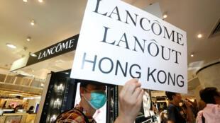 圖為香港示威者在蘭蔻專賣店前示威,標語牌上寫着蘭蔻滾出香港