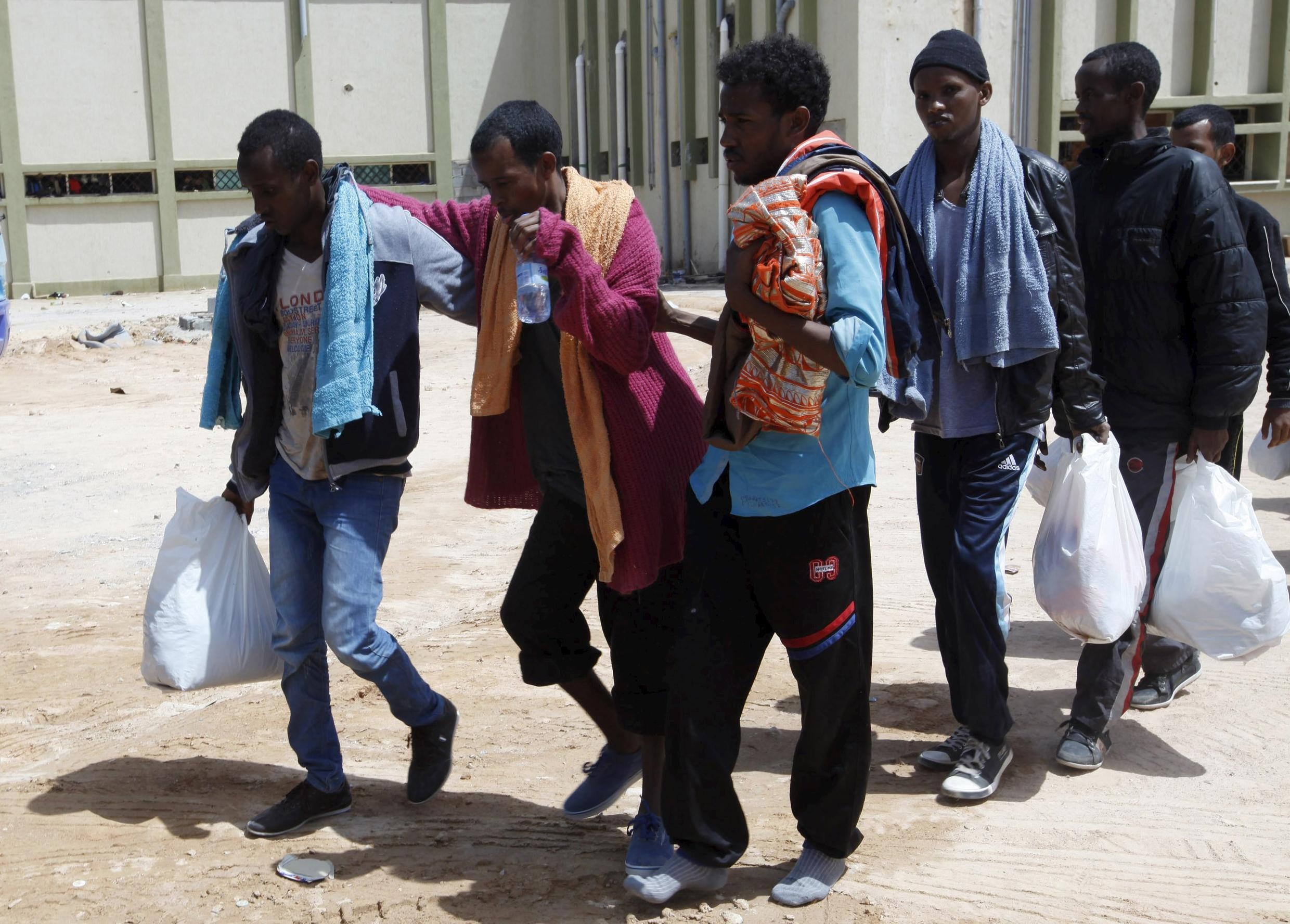 Migrants help another migrant walk to a bus bound for an immigration centre in the coastal city of Misrata, Libya, May 9, 2015.