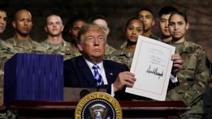 Tổng thống Donald Trump giơ cao văn bản luật quốc phòng vừa ký trước các quân nhân Mỹ tại căn cứ Fort Drum, New York, 13/08/2018.