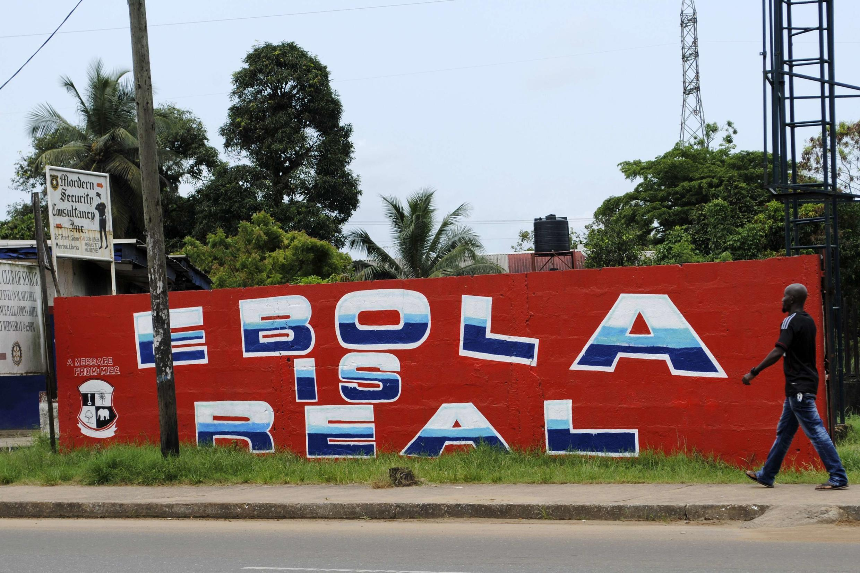 """Cartaz em muro em Monróvia, na Libéria, afirma:""""O Ebola é real""""."""