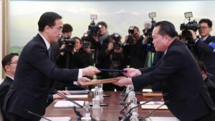 Troca de documentos entre os chefes da delegação norte-coreana, Ri Son Gwon e o sul-coreano Cho Myoung-gyon após o encontro em Panmunjom, zona desmilitarizada que separa as duas Coreias, 9 de janeiro. de 2018.