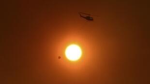 Un hélicoptère chargé d'eau pour la lutte contre l'incendie qui frappe la région de Sydney, le 20 octobre 2013.