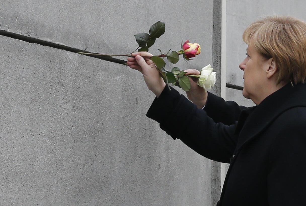 Angela Merkel deposita flor no que sobrou do Muro de Berlim, em memória dos dissidentes que morreram tentando entrar na Alemanha Ocidental