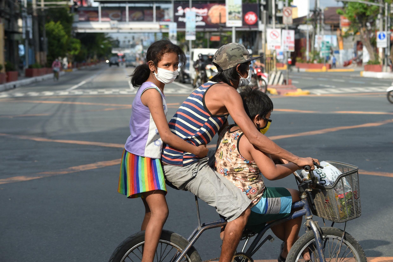 Un père et ses deux enfants dans les rues de Manille, le 20 mars 2020.