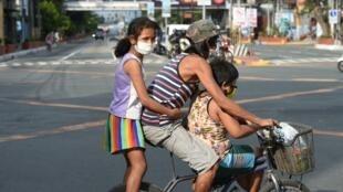 Des enfants et leur père dans les rues de Manille