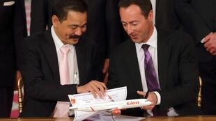 Airbus CEO Fabrice Bregier (R) and Lion Air CEO Rusdi Kirana (L) sign a contract at the Elysee Palace in Paris