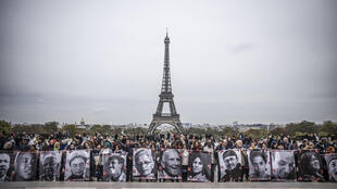 More than 150 rights campaigners from around the world gather at the foot of the Eiffel Tower at end of world summit, Wednesday 31 October