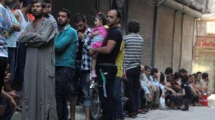 La gente hace cola para conseguir pan en el barrio rebelde Al-Shaar, en Alepo.