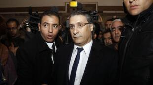 """Nabil Karoui (ao centro), dono do canal de TV Nessma, que exibiu o filme """"Persepolis"""", chega ao tribunal em Tunis."""