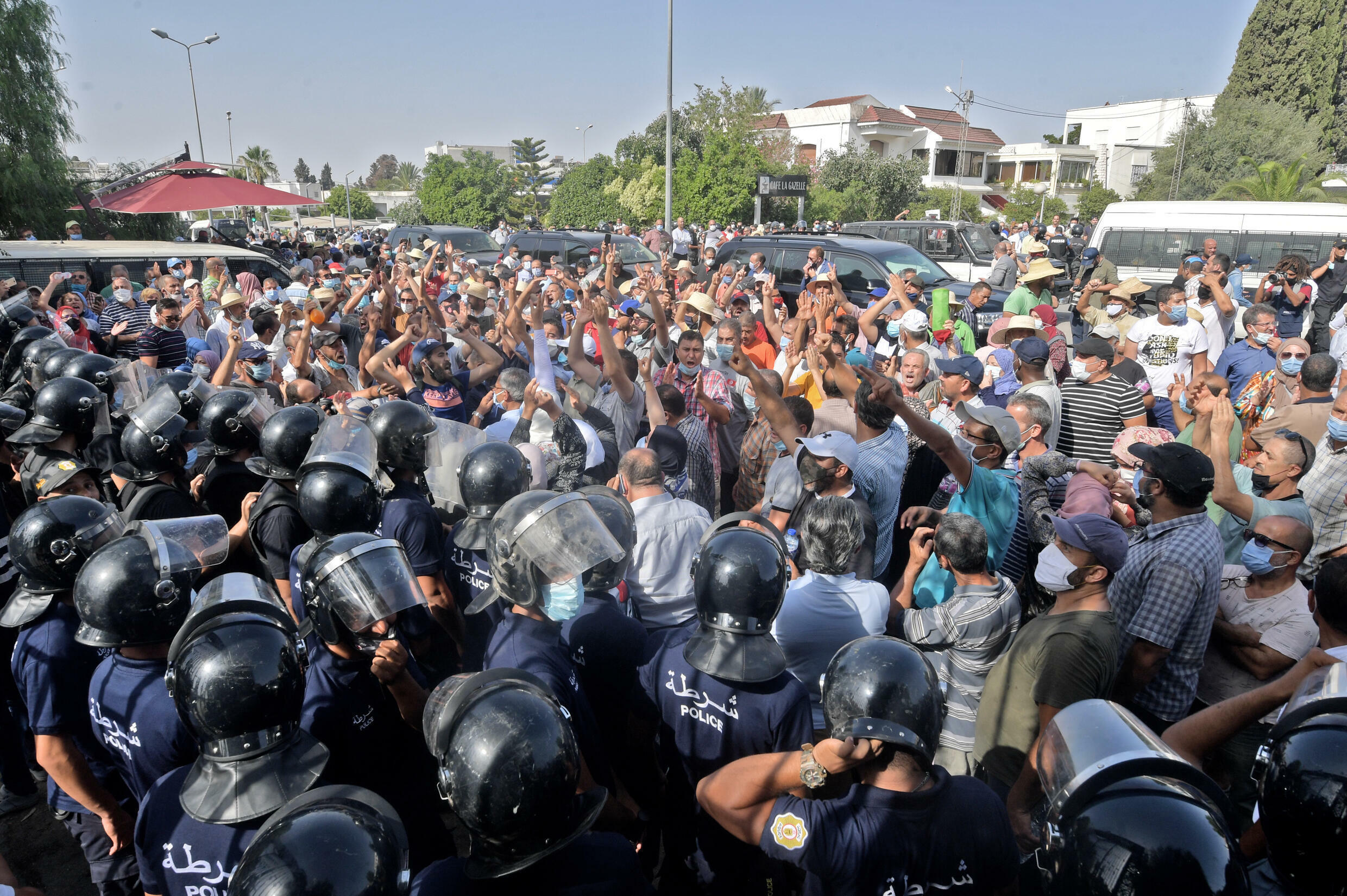 Tunisian security officers hold back protesters outside the parliament building on July 26, 2021 after President Kais Saied suspended the legislature